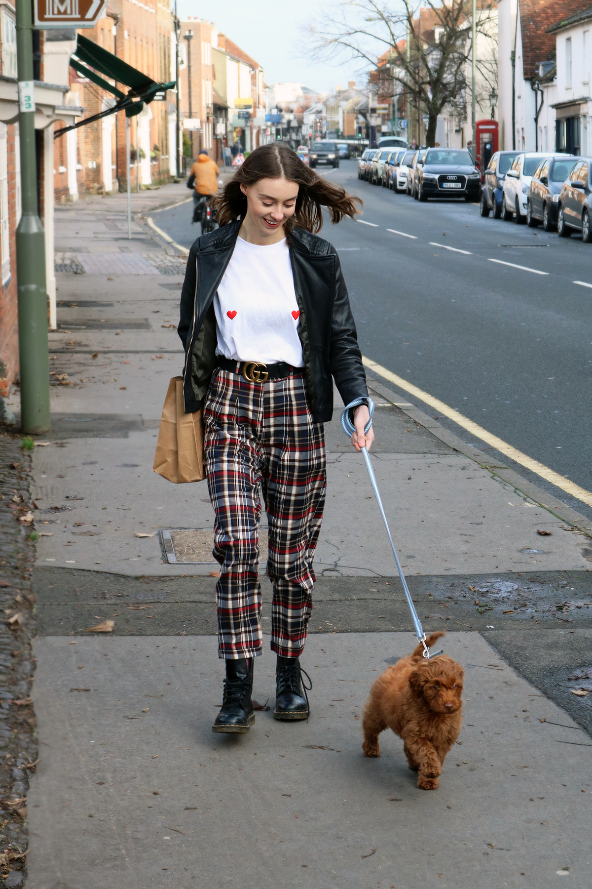 Grace Mandeville walking red Australian labradoodle puppy, wearing gucci belt, tartan trousers, coppafeel top